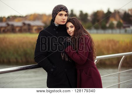 Happy young couple in love walking outdoor. Male and female fashion model. Young man and woman embracing