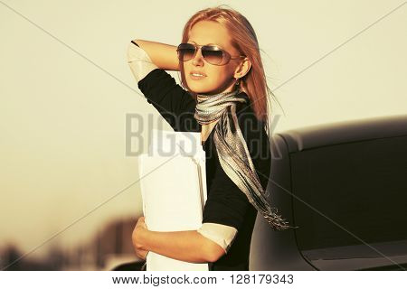 Young business woman in sunglasses next to her car. Female blond fashion model outdoor