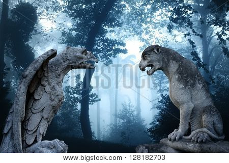 Ancient eagle statue and lion statues in mysterious landscape of foggy forest