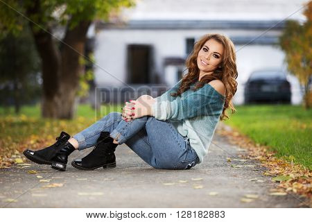 Happy young fashion woman with long curly hairs sitting on city street. Female fashion model outdoor