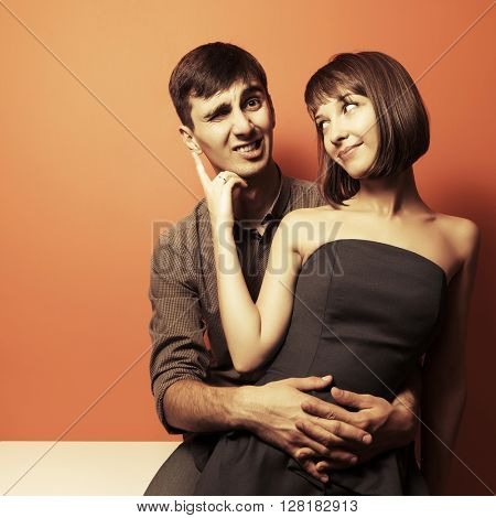 Happy young couple in love sitting on the desk at apartment. Male and female fashion model indoors. Young man and woman embracing