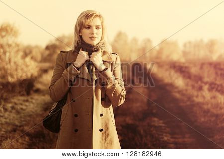 Happy blond fashion woman walking in autumn field. Female blond fashion model with handbag in beige classic coat outdoor