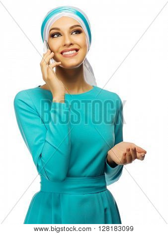 Young muslim woman in blue dress with mobile phone isolated
