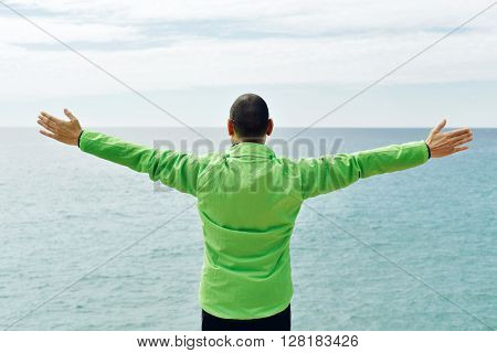 a young caucasian man wearing sport clothes seen from behind with his arms in the air in front of the ocean, feeling free