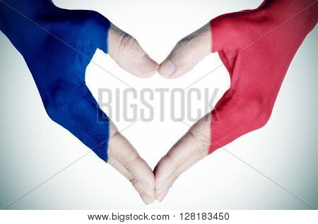 closeup of the hands of a young woman forming a heart patterned as the flag of France, with a vignette added