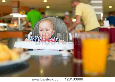 Baby girl eating lunch on the high chair