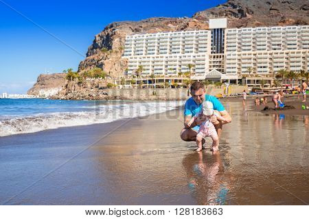 First steps of little baby girl with his father at the beach