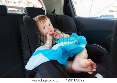 Baby boy in the car on child safety seat