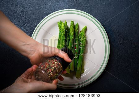 Cooked asparagus served on a plate over dark  background