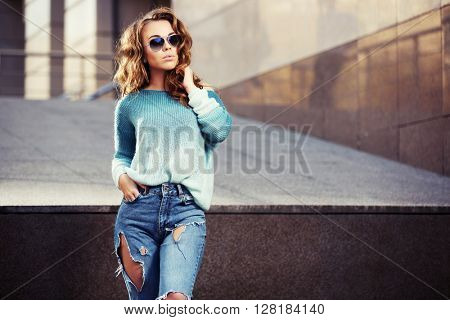 Happy young fashion woman in sunglasses walking on city street. Female fashion model in ripped jeans outdoor