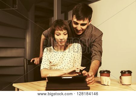 Young business couple with tablet computer at office. Young man and woman indoors