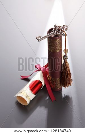 round certificate holder, certificate and key with tassel on the gray background