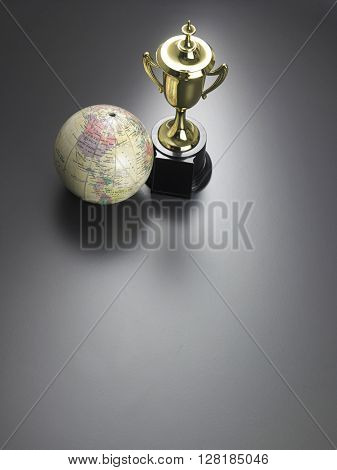 trophy and desk globe on the gray background