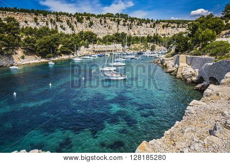 Picturesque narrow fjords between stony coast. White sailing yachts wait for the owners.  National Park Calanques on the Mediterranean coast