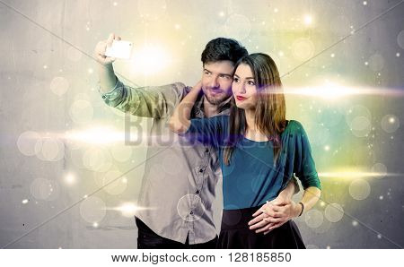 A fresh happy couple taking selfie photo with mobile phone in front of colorful lights glitter wall background concept