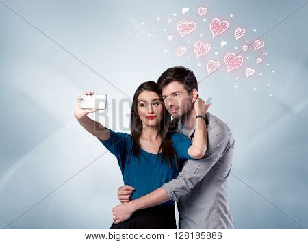 A young couple in love and drawn red hearts taking selfie with a mobile phone in the handsome guy's hand in front of an empty clear grey wall background concept