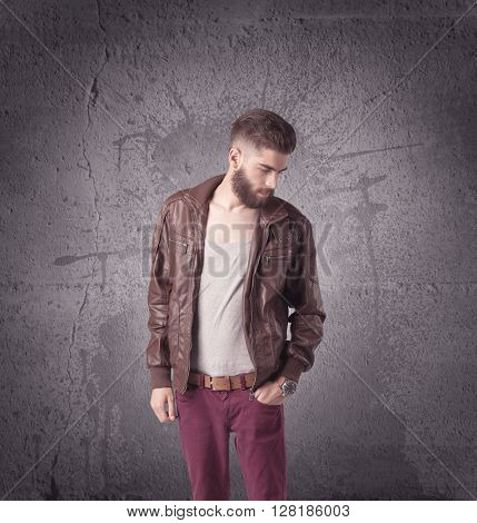 A hipster fashion model guy in casual clothing stnading with mobile phone in front of concrete urban wall background concept
