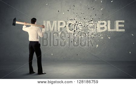 Business man hitting impossible sign with hammer on grungy wall