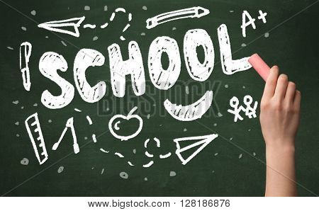 A teacher writing school, drawing children things on clean green chalkboard by hand