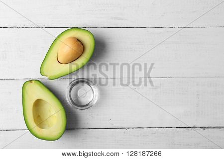 Fresh avocado oil on wooden table, top view