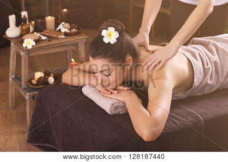 Beautiful young girl having massage in spa salon
