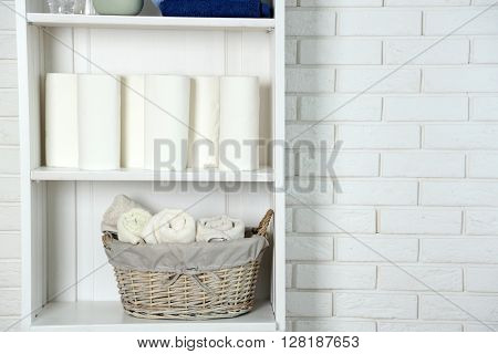 Bathroom set with towels and basket on a shelf in light interior