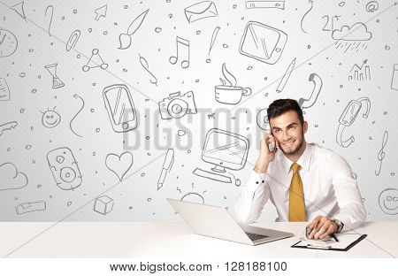 Businessman sitting at table with hand drawn media icons and symbols
