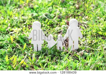 Cutout figurine of a family on green grass background