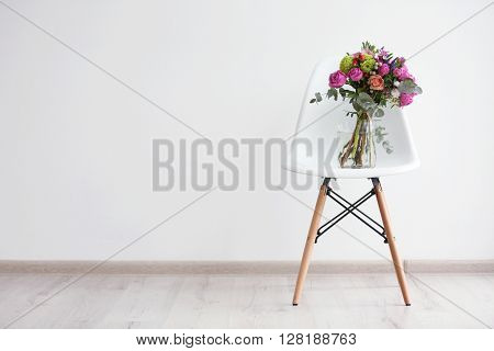 Bouquet of roses on a white chair in room