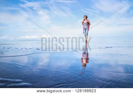 Young lady walking on a wet sandy beach with rucksack