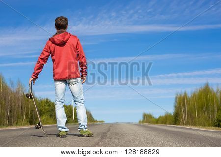 Young man standing with a skateboard at sunny day