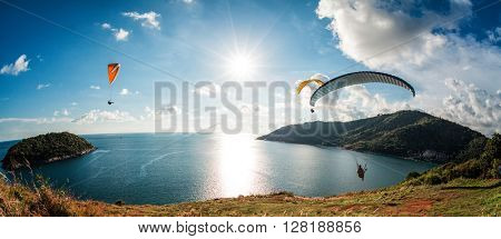 Three Skydiver flying over the water during sunset with the mountains