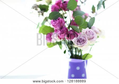 Beautiful bouquet of roses on light blurred background