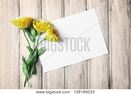 White sheet and yellow blossom on blue wooden background, empty space