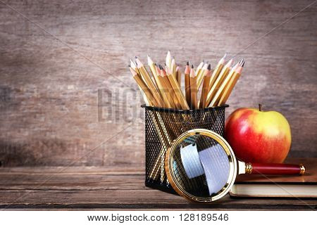 Set of pencils in metal holder, book, magnifier and apple on wooden background