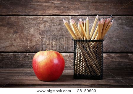 Set of pencils in metal holder and fresh apple on wooden background