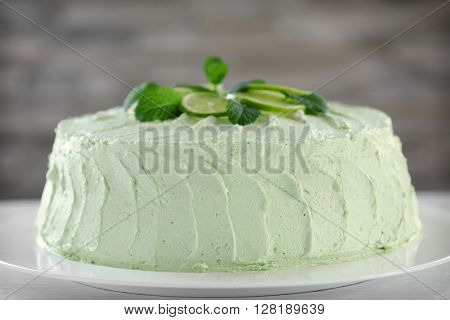 Delicious creamy lime cake on blurred background