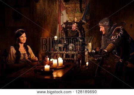 Medieval king and his subjects communicate in the hall of the castle.