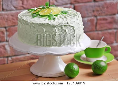 Lime cake on white stand beside brick wall