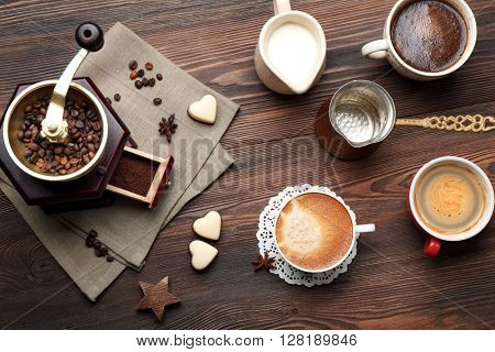 Cups of coffee with beans on wooden table, top view