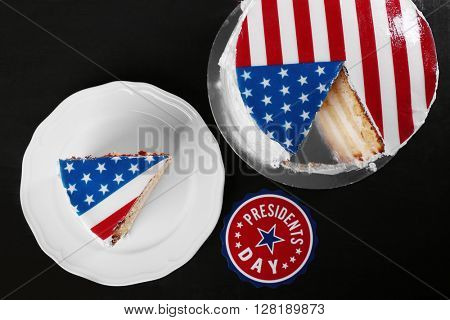 Piece of American flag cake, on black wooden background. President's day concept.
