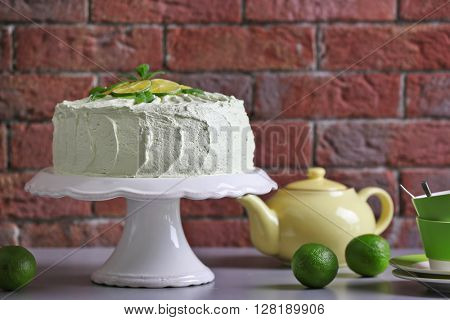 Lime cake and tableware beside red brick wall