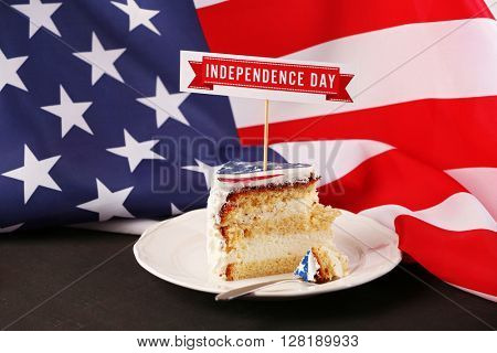 Piece of American flag cake, on black wooden table. Independence day concept.