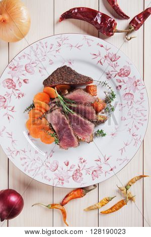 Rare beef steak, cut in slices, with carrot and aromatic herbs