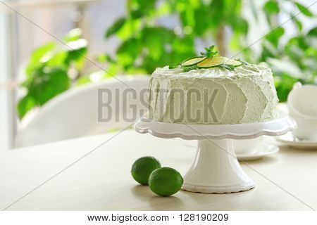 Lime cake on a white stand.
