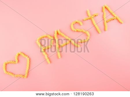 Pasta word made with fusilli on pink background