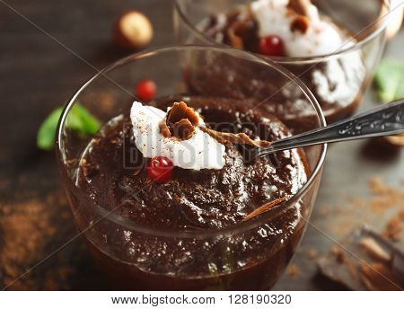 Glass cup of chocolate dessert with frothed milk and cranberries on black wooden table