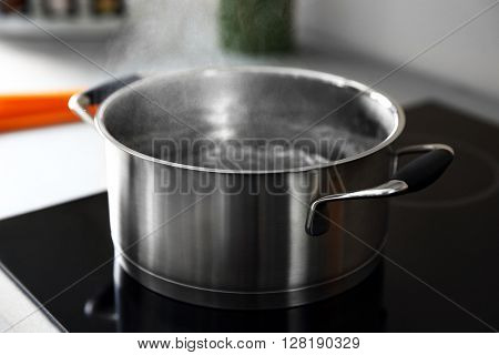 Boiling water in pan on electric stove in the kitchen