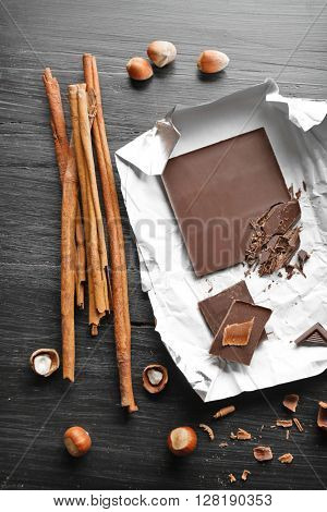 Pieces of chocolate with hazelnuts and cinnamon on black wooden background