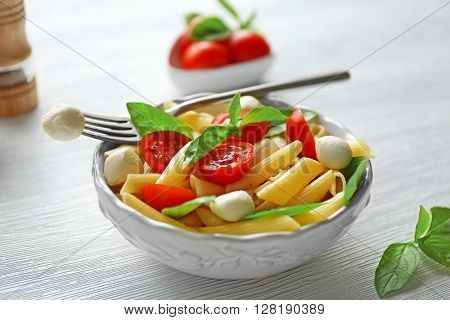 Cooked penne pasta with mozzarella, fresh tomatoes and basil in white bowl on wooden table